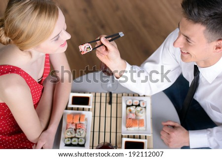 Couple eating sushi. Beautiful young couple sitting together at the restaurant and eat sushi - stock photo