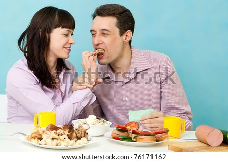 Couple eating together on kitchen - stock photo