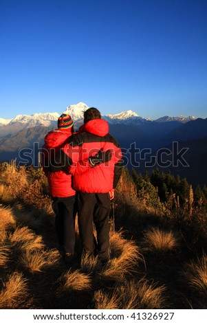 Couple embrace as they watch the sunrise on poonhill - Nepal - stock photo