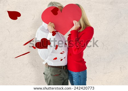 Couple embracing and holding heart over faces against parchment - stock photo