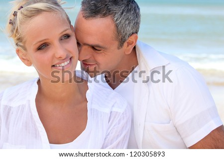 Couple embracing by the sea - stock photo