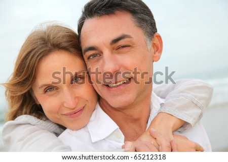 Couple embracing each other at the beach - stock photo