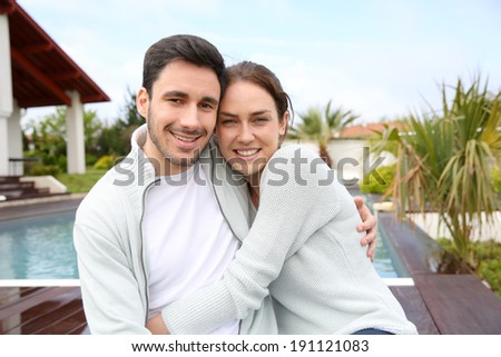 Couple embracing each other in front of house - stock photo