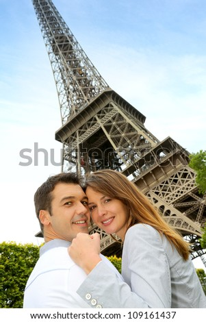 Couple embracing each other in front of the Eiffel tower - stock photo