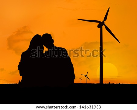 Couple embracing in front of a sunset with silhouettes of wind turbines - stock photo