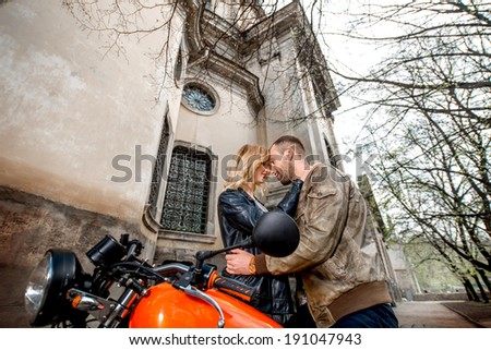 Couple embracing near the motorcycle on the old city background - stock photo