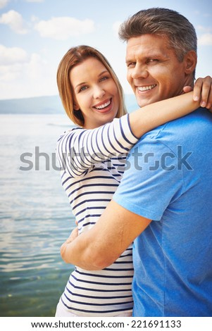 Couple embracing near water - stock photo
