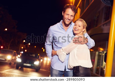 Couple embracing on city street at night, portrait - stock photo
