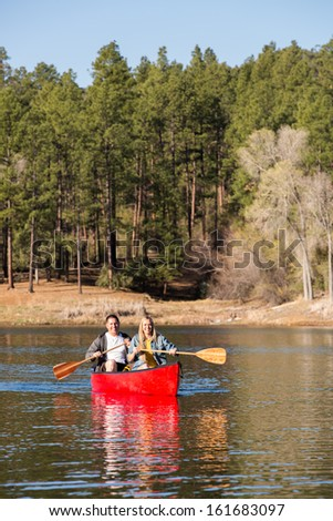 Couple Enjoying a Fun Paddle on the Lake in a Canoe - stock photo
