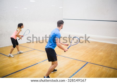 Couple enjoying a game of squash in the squash court - stock photo
