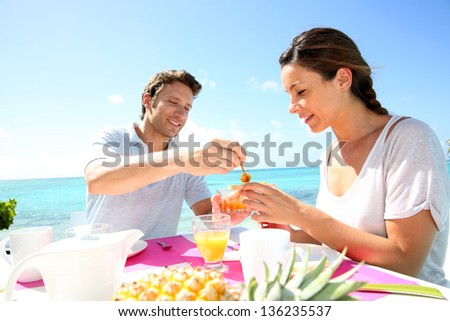 Couple enjoying breakfast in resort - stock photo