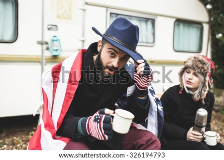 Couple enjoying cold autumn days in nature in front of their trailer and drinking hot tea  - stock photo