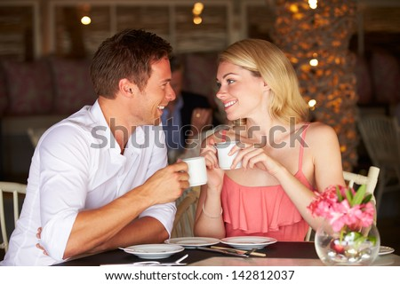 Couple Enjoying Cup Of Coffee In Restaurant - stock photo
