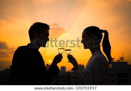 Couple enjoying glass of wine with city view - stock photo