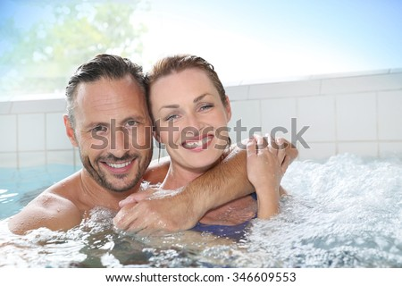 Couple enjoying hot tub bath in spa center - stock photo