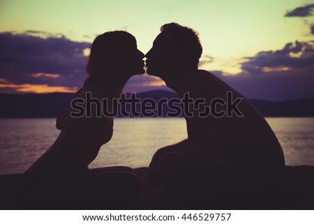 Couple enjoying on the beach in sunset / sunrise time. - stock photo