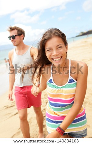 Couple enjoying romantic beach vacation holiday, Young modern trendy cool multi-ethnic couple having fun laughing together smiling happy. mixed race Asian woman, Caucasian man. - stock photo