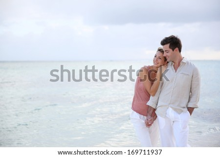 Couple enjoying sunset time at the beach - stock photo