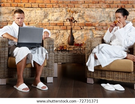 Couple enjoying wellness room in bathrobe, sitting together in armchair, using laptop computer, having tea.? - stock photo
