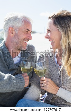 Couple enjoying white wine on picnic at the beach smiling at each other on a bright but cool day - stock photo