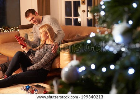 Couple Exchanging Gifts By Christmas Tree - stock photo