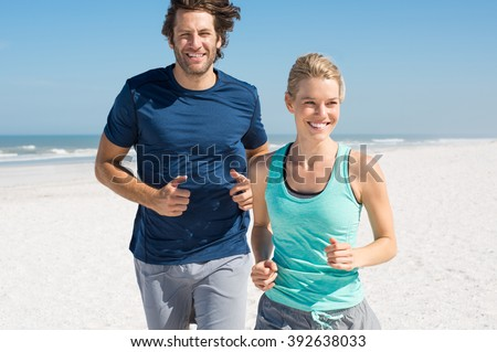 Couple exercising at beach. Trainer training athlete for fitness. Athletics jogging in summer sport shorts enjoying the sun. - stock photo