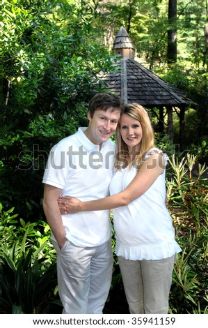 Couple expecting their first child embrace on a wooden path in the Birmingham Botanical Garden in Birmingham, Alabama. Both are wearing khakis and white shirts. - stock photo