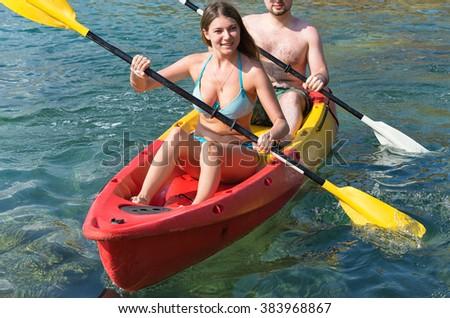 Couple exploring calm tropical bay by kayak.  - stock photo