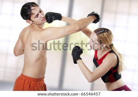 Couple fighters workout. Female punching man - stock photo