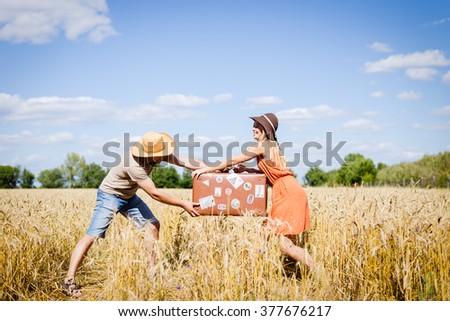 Couple fighting in field holding suitcase on countryside landscape blue sky outdoors background.  - stock photo