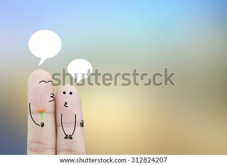 Couple finger holding flower on blurred background - stock photo