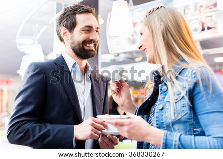Couple flirting at date drinking coffee in cafe - stock photo