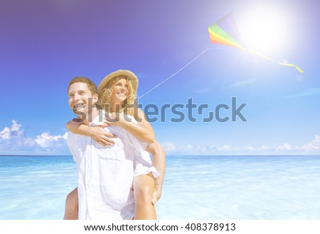 Couple flying a kite on the beach. - stock photo