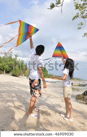 couple flying kites in small fishing village seaside - stock photo