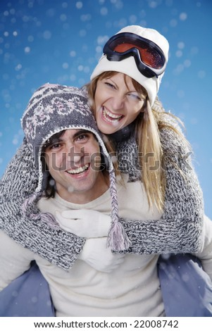 couple fooling around in the snow - stock photo