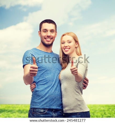 couple, gesture and family concept - smiling couple showing thumbs up - stock photo