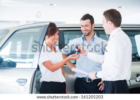 Couple getting car keys from a car seller - stock photo