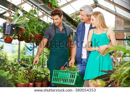Couple getting consultation in nursery shop from a gardener - stock photo