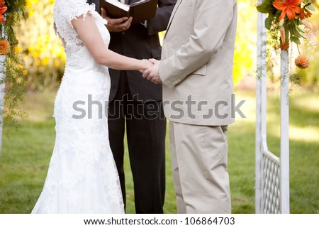 Couple Getting Married at an Outdoor Wedding Ceremony - stock photo
