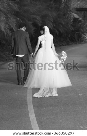 couple getting married shot outdoor in a field with selective focus in black and white - stock photo