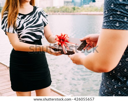 Couple giving a gift box to each other. Happy relationship in outdoor scene. Love and relationship concept - stock photo