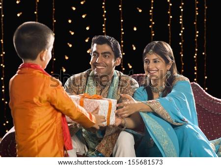 Couple giving Diwali gift to their son - stock photo