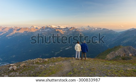 Couple hand in hand watching the stunning panorama on the Alps at sunset. Wide angle view from above with glowing mountain peaks and glaciers in the background. Valle d'Aosta, Italy. - stock photo