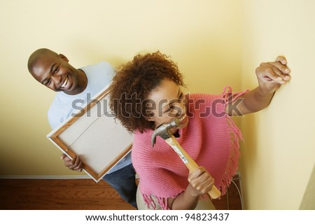 Couple hanging picture - stock photo