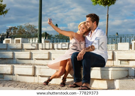 Couple having a city break in summer sitting on a brick wall in the sunlight, making pictures - stock photo