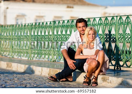 Couple having a city break in summer sitting on a bridge over a river in the evening light - stock photo