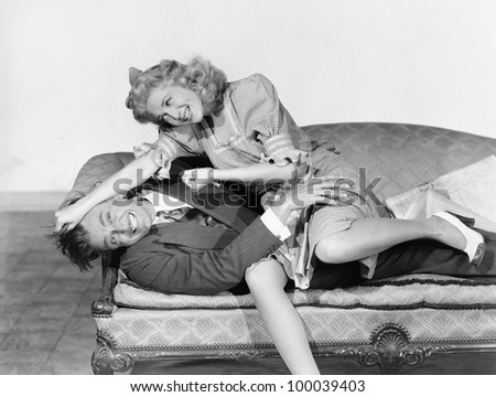 Couple having a playful fight on a couch - stock photo