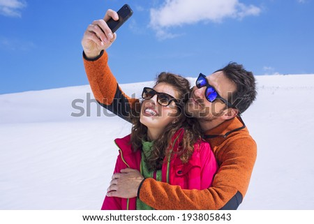 couple having a selfie on the snow - stock photo