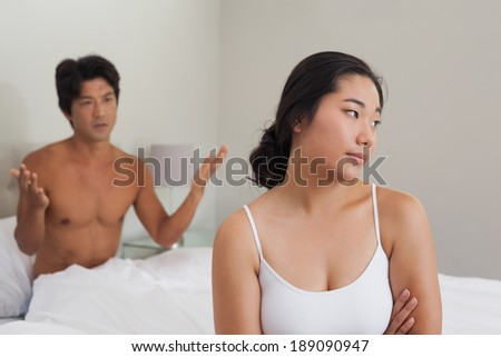 Couple having an argument in bed at home in bedroom - stock photo