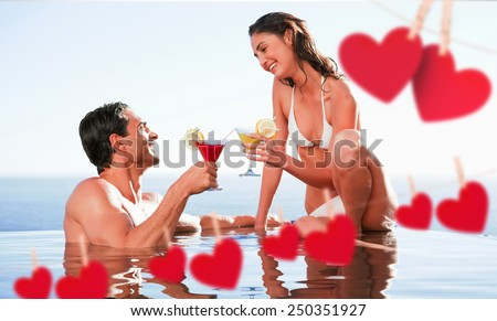 Couple having cocktails in the pool against hearts hanging on a line - stock photo